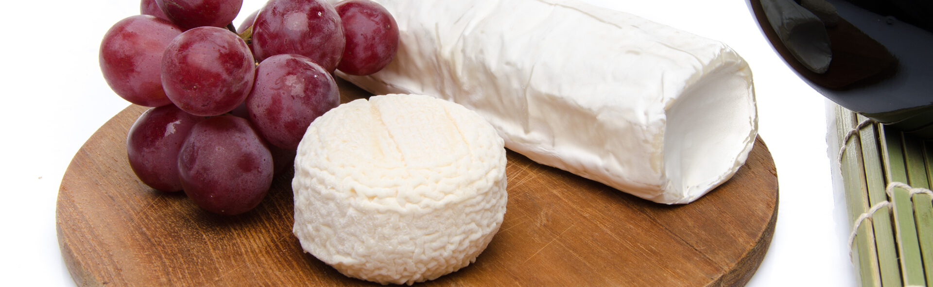 Photo of Holy Goat cheese and grapes on a wooden cutting board.